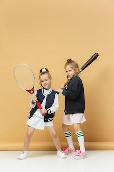 Retrato de duas meninas como tenistas segurando a raquete de tênis.