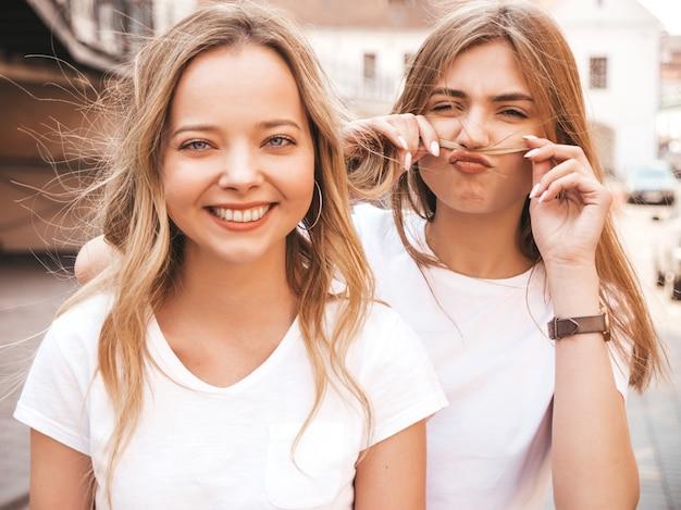 Retrato de duas meninas de hipster loira sorridente jovem bonita em roupas de camiseta branca na moda verão. . modelos positivos se divertindo