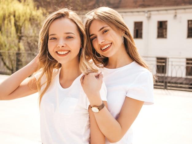 Retrato de duas meninas de hipster loira sorridente jovem bonita em roupas de camiseta branca na moda verão. . modelos positivos se divertindo.