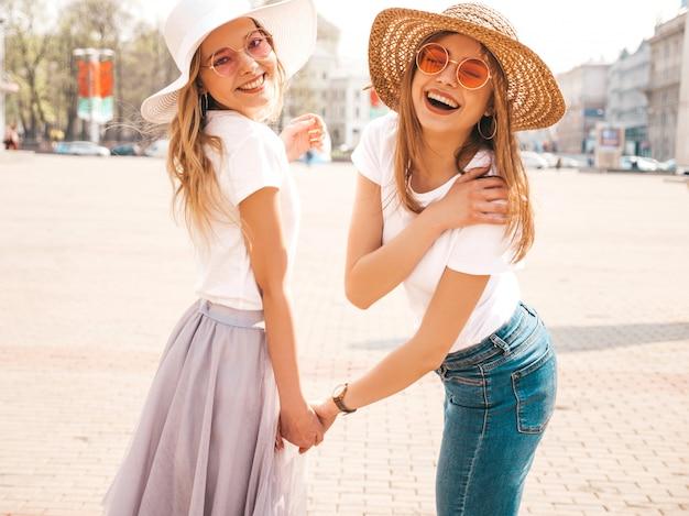 Retrato de duas meninas de hipster loira sorridente jovem bonita em roupas de camiseta branca na moda verão. . modelos positivos, segurando um ao outro mão