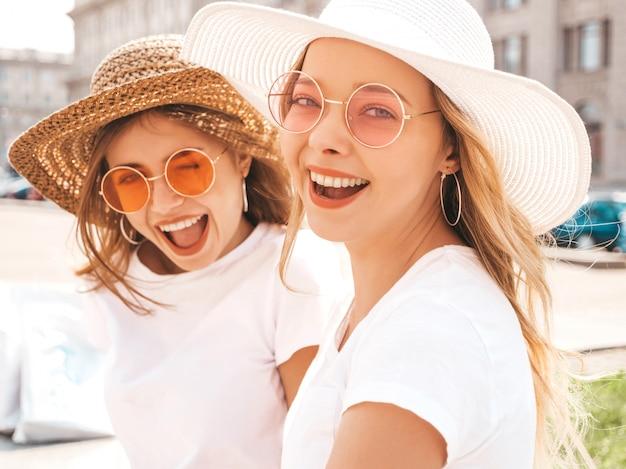 Retrato de duas meninas de hipster loira sorridente jovem bonita em roupas de camiseta branca na moda verão.