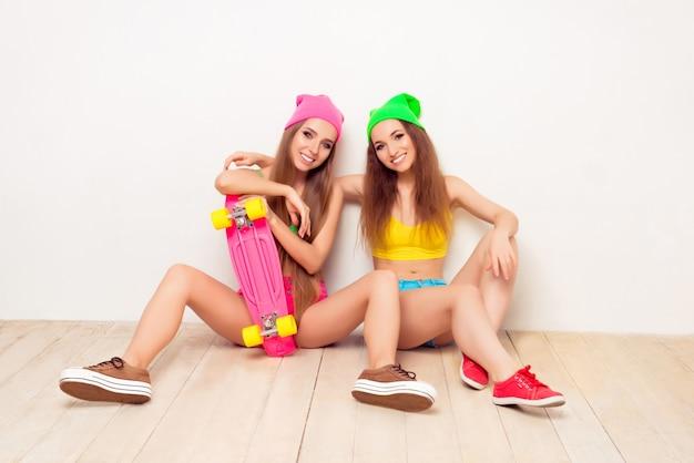 Retrato de duas meninas elegantes e felizes sentadas no chão com skate