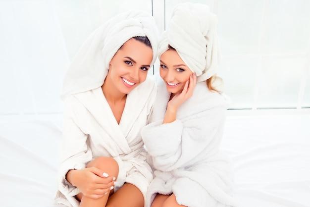 Retrato de duas meninas felizes e sorridentes em roupões de banho e turbantes