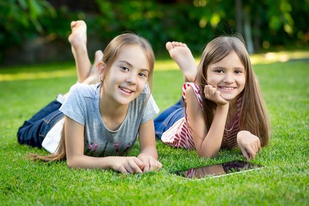 Retrato de duas meninas felizes usando tablet digital na grama do parque