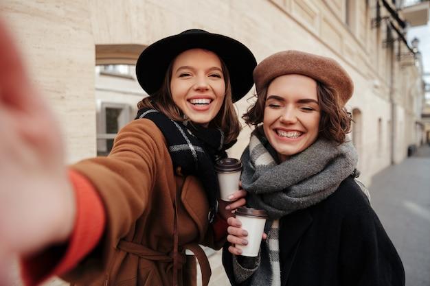 Retrato de duas meninas felizes, vestidas com roupas de outono