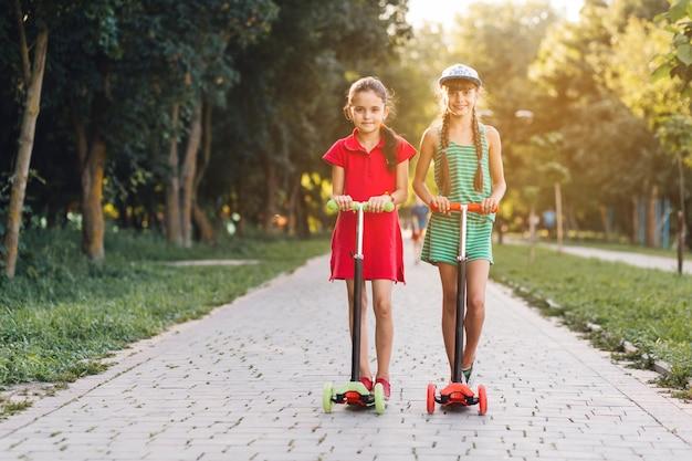 Retrato, de, duas meninas, ficar, ligado, empurrar scooter, parque