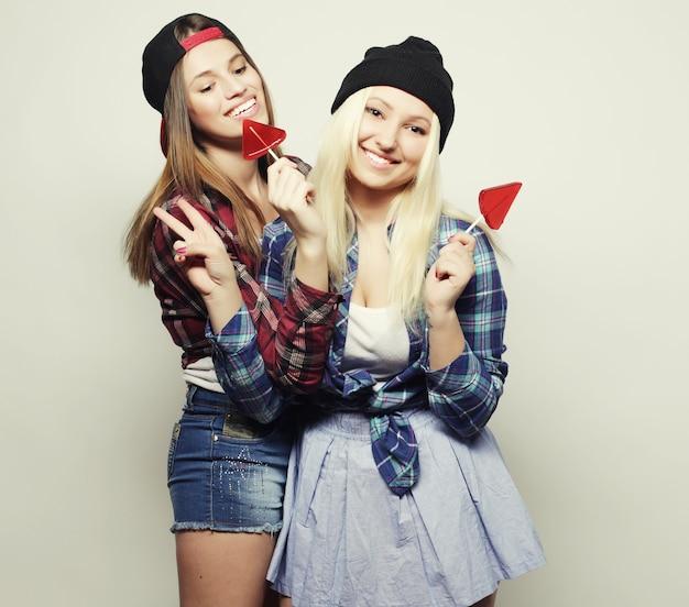 Retrato de duas meninas jovens bonitas hippie com chapéus e óculos de sol segurando doces. retrato de estúdio de dois melhores amigos alegres, se divertindo e fazendo caretas.