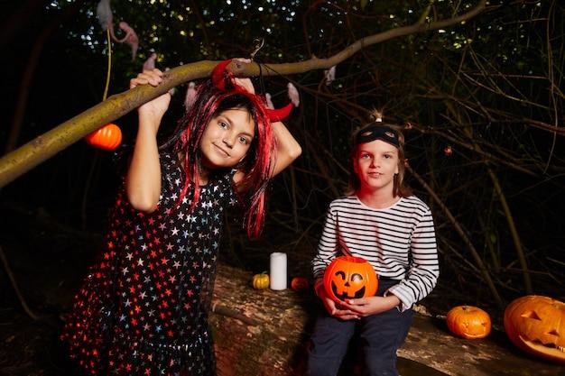 Retrato de duas meninas sentadas ao ar livre no escuro durante a festa de halloween