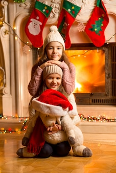 Retrato de duas meninas sorridentes sentadas ao lado da lareira na véspera de natal
