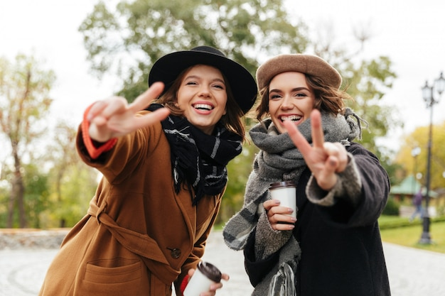 Retrato de duas meninas sorridentes, vestidas em casacos