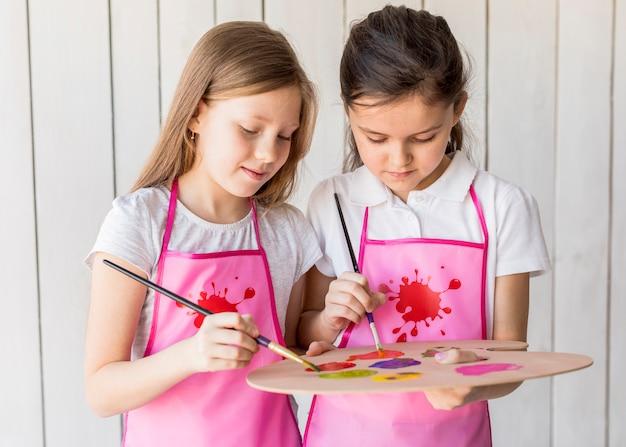 Retrato, de, duas meninas, usando, paleta, pintar, com, pincel