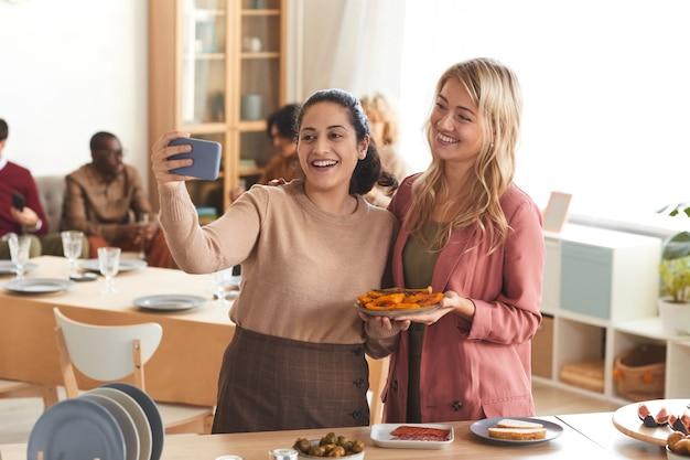 Retrato de duas mulheres adultas alegres tirando foto de selfie dentro de casa enquanto desfruta de um jantar com amigos,