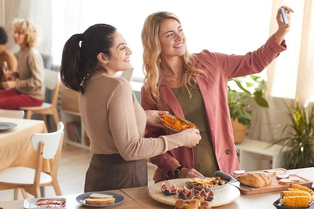 Retrato de duas mulheres adultas modernas tirando uma selfie dentro de casa enquanto desfrutam de um jantar com amigos.
