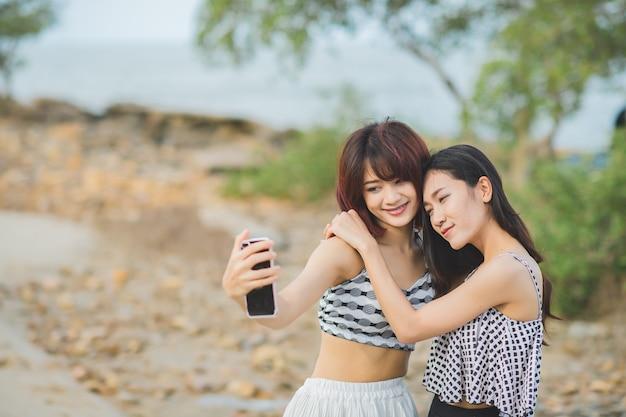 Retrato de duas mulheres asiáticas em selfie de maiô por telefone na praia