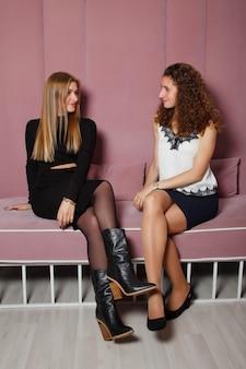 Retrato de duas mulheres bonitas loiras e morenas na sala, sentadas no sofá rosa e olhando uma para a outra
