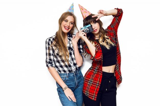 Retrato de duas mulheres bonitas posando na parede branca com chapéus de festa