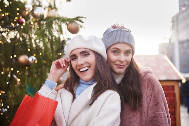 Retrato de duas mulheres com roupas quentes no mercado de natal