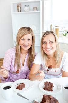 Retrato de duas mulheres comendo um bolo de chocolate durante o lanche