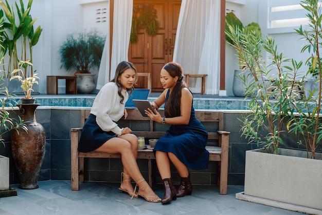 Retrato de duas mulheres de negócios que se sentam em um banco com alguns coquetéis e usam um tablet.