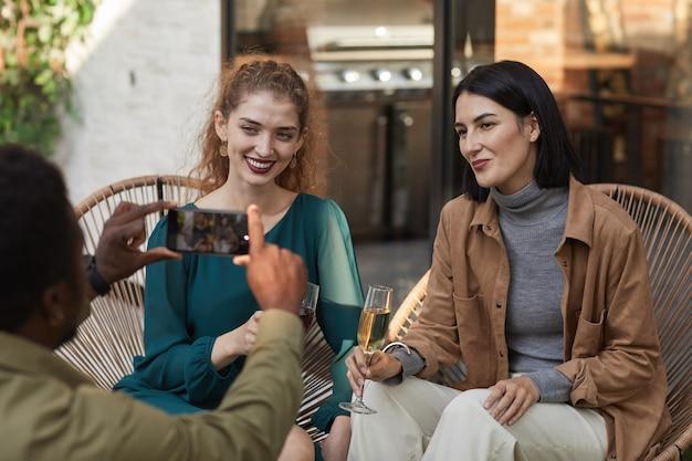 Retrato de duas mulheres elegantes posando para a foto e sorrindo para a câmera enquanto desfruta de uma festa ao ar livre.