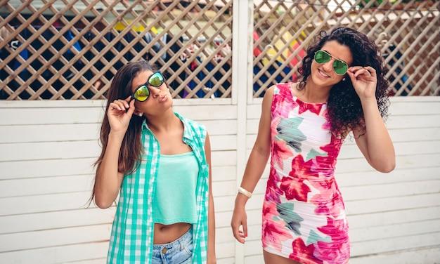 Retrato de duas mulheres felizes com óculos escuros posando sobre a cerca branca do jardim