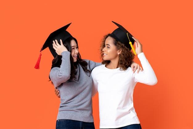 Retrato de duas mulheres felizes de raça mista se formar segurando lá bonés de formatura, olhando um ao outro na parede isolada laranja