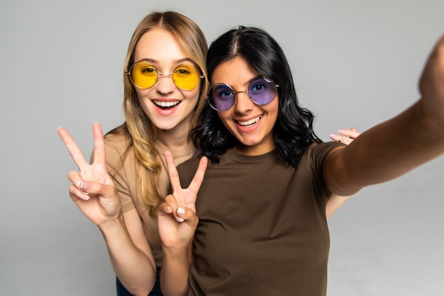 Retrato de duas mulheres felizes fazendo foto de selfie no smartphone enquanto mostra o sinal de dois dedos na parede cinza