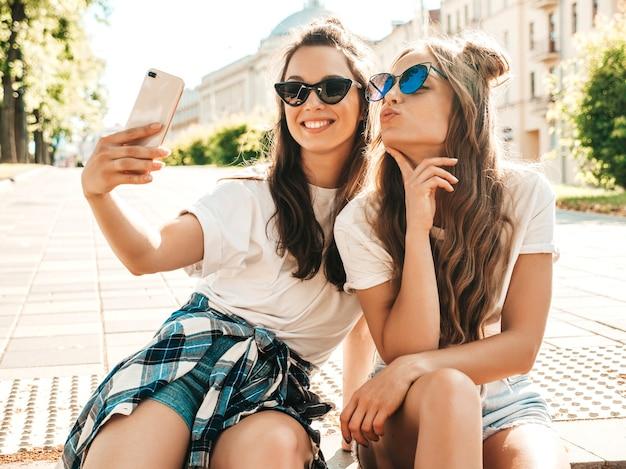 Retrato de duas mulheres jovens e bonitas sorridentes hippie em roupas da moda de verão camiseta branca