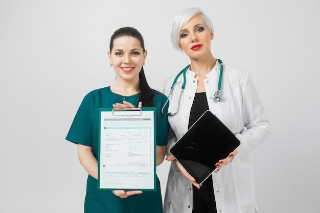 Retrato de duas mulheres jovens em traje de médicos isolado na