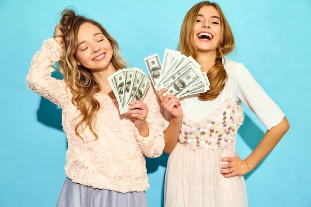 Retrato de duas mulheres loiras felizes felizes vestindo roupas de verão, regozijando-se ganhar e segurando dinheiro isolado sobre a parede azul