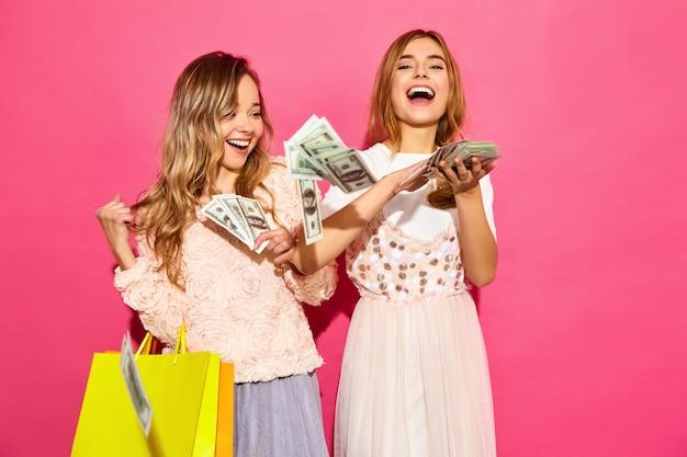 Retrato de duas mulheres loiras sorridentes elegantes jovens segurando sacolas de compras. mulheres vestidas com roupas de verão hipster. modelos positivos gastando dinheiro na parede rosa