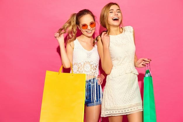 Retrato de duas mulheres loiras sorridentes elegantes jovens segurando sacolas de compras. mulheres vestidas com roupas de verão hipster. modelos positivos posando sobre blackground rosa