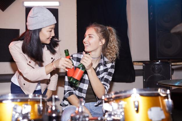 Retrato de duas mulheres modernas batendo garrafas de cerveja no estúdio de música