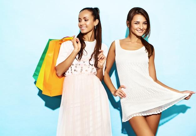 Retrato de duas mulheres morenas sorridentes elegantes jovens segurando sacolas de compras. mulheres vestidas com roupas de verão hipster. positivos modelos posando sobre parede azul