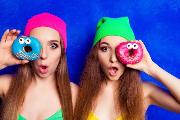 Retrato de duas mulheres muito chocadas segurando donutes perto do olho