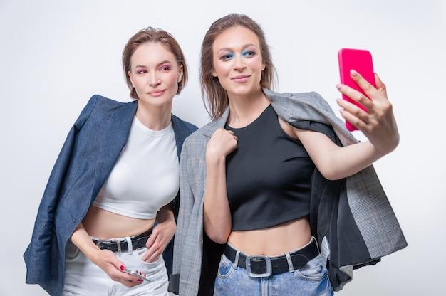 Retrato de duas mulheres rindo em blazers tomando uma selfie. conceito de amizade. mídia mista