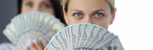 Retrato de duas mulheres segurando um leque de notas de dólar na frente do rosto