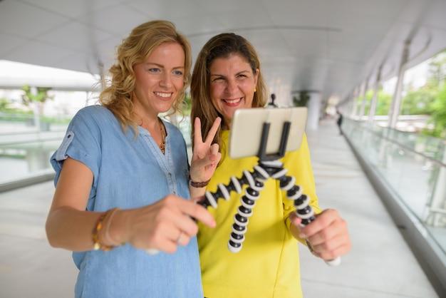 Retrato de duas mulheres vlogging e tomar selfie com telefone móvel juntos ao ar livre