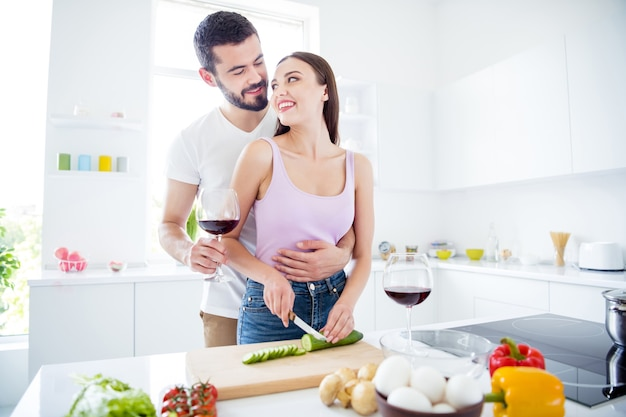 Retrato de duas pessoas apaixonadas homem segurando copo vinho abraçar mulher cortar faca