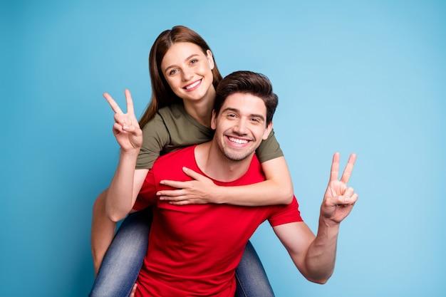 Retrato de duas pessoas casadas positivas relaxam descanso no feriado de 14 de fevereiro homem abraço nas costas sua namorada fazer v-sinais usar camiseta vermelha verde isolada sobre fundo de cor azul