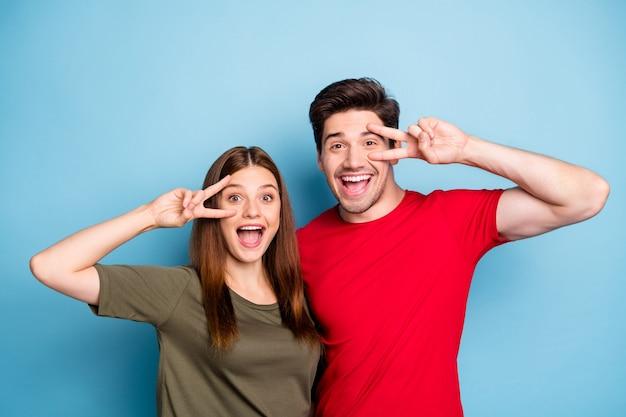 Retrato de duas pessoas cônjuges diversão nos fins de semana de verão, relaxar, descansar, fazer sinais v perto do rosto, usar roupas de estilo casual isoladas sobre fundo de cor azul