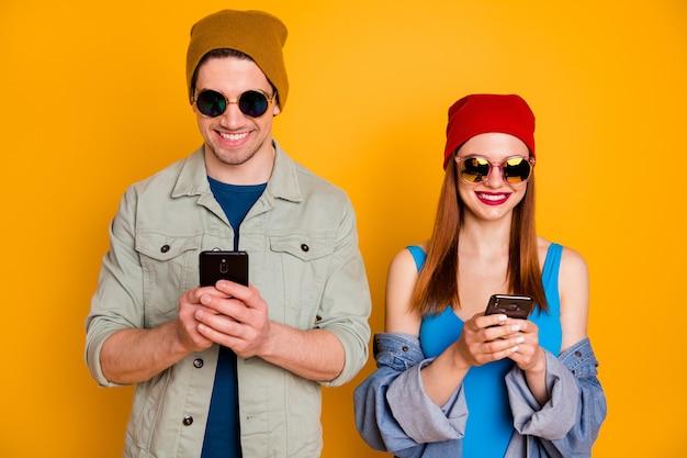 Retrato de duas pessoas positivas, estudantes, blogueiros, homem, mulher, usar smartphone, mensagens, digitando, mídias sociais, usar óculos de sol, camisa, jeans, jaqueta, isolado, brilhante, cor, fundo