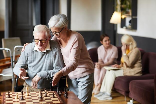 Retrato de duas pessoas sêniors jogando xadrez e desfrutando de atividades em um lar de idosos.