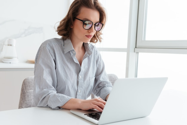 Retrato de e-mail de mensagens de texto elegante jovem no laptop enquanto está sentado na mesa na sala de luz