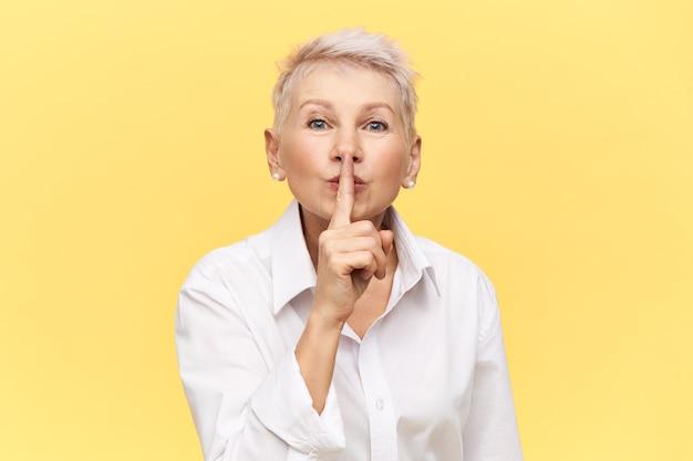 Retrato de elegante atraente mulher de negócios de meia idade na camisa branca, segurando o dedo da frente nos lábios, pedindo-lhe para manter silêncio sobre o segredo comercial, fazendo shh gesto.