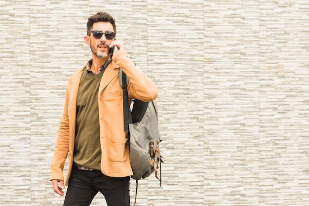 Retrato, de, elegante, posição homem, contra, parede, com, seu, mochila, falando telefone móvel