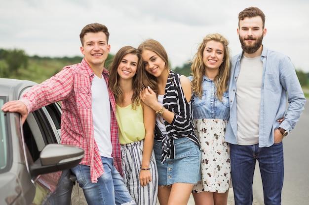Retrato de elegantes jovens amigos posando perto do carro estacionado