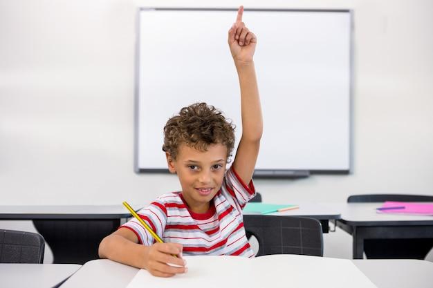 Retrato, de, elementar, menino, levantando mão, em, sala aula