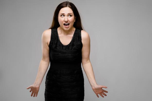 Retrato de emocional bastante confuso confuso surpreso e mais tamanho modelo em pé no estúdio em cinza