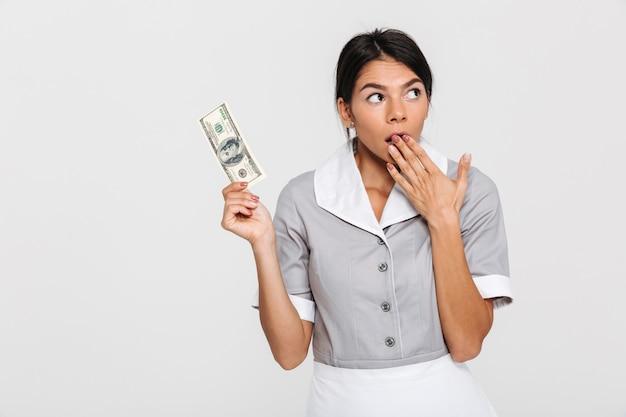 Retrato de empregada atraente espantado em uniforme segurando cem dólares enquanto cobre a boca com a mão, olhando de lado